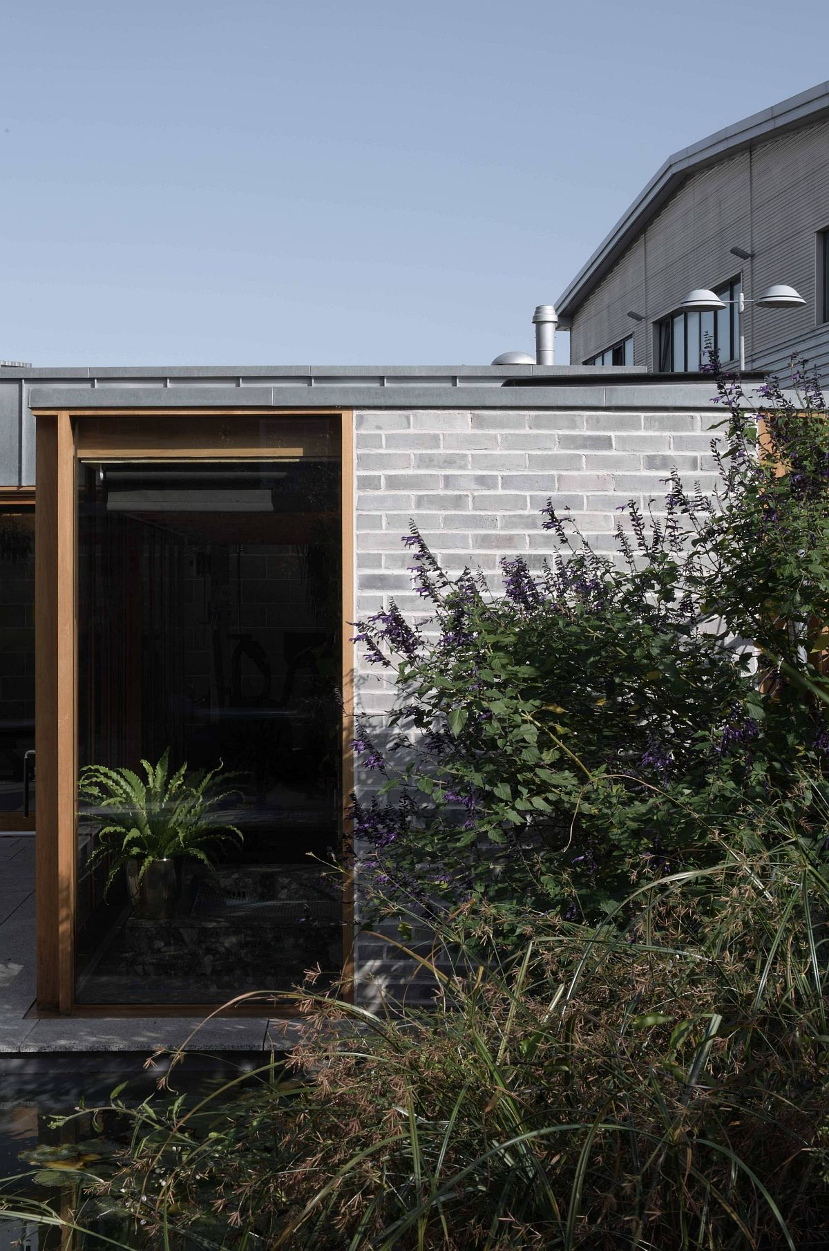 Exposed blockwork walls, wood and glass shpe the lovely backyard escape