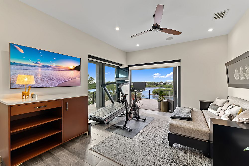 Gray and white home gym with views that end up stealing the spotlight