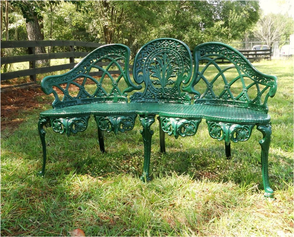 Green metal bench on grass