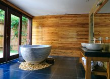 Grey tub on stones with glass doors and wooden walls