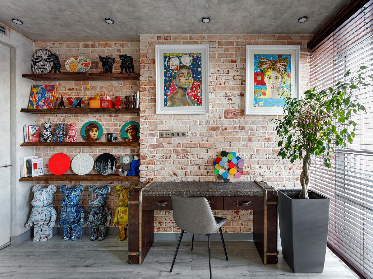 Industrial home office with modern decor and a brick wall backdrop