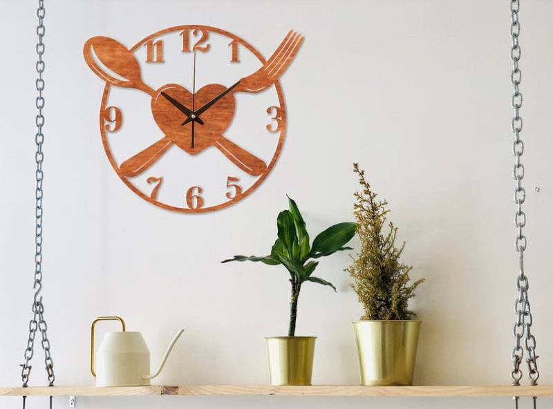 Kitchen wall clock with spoon, fork and heart design hanging on top of a shelf with plants