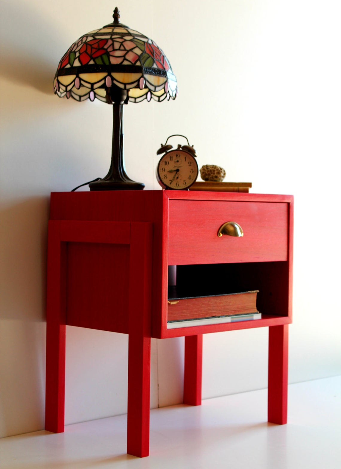 Lampshade and clock on top of a red drawer