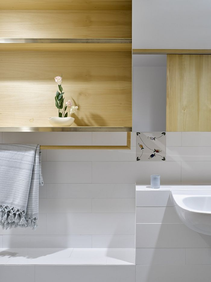 Light wood elements in the bathroom bring elegance and warmth to the white space