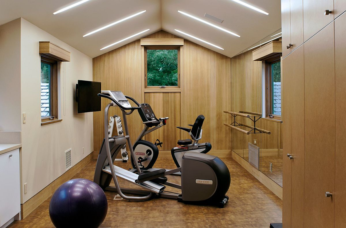Lighting plays a big role in giving this home gym in white a spacious, modern look