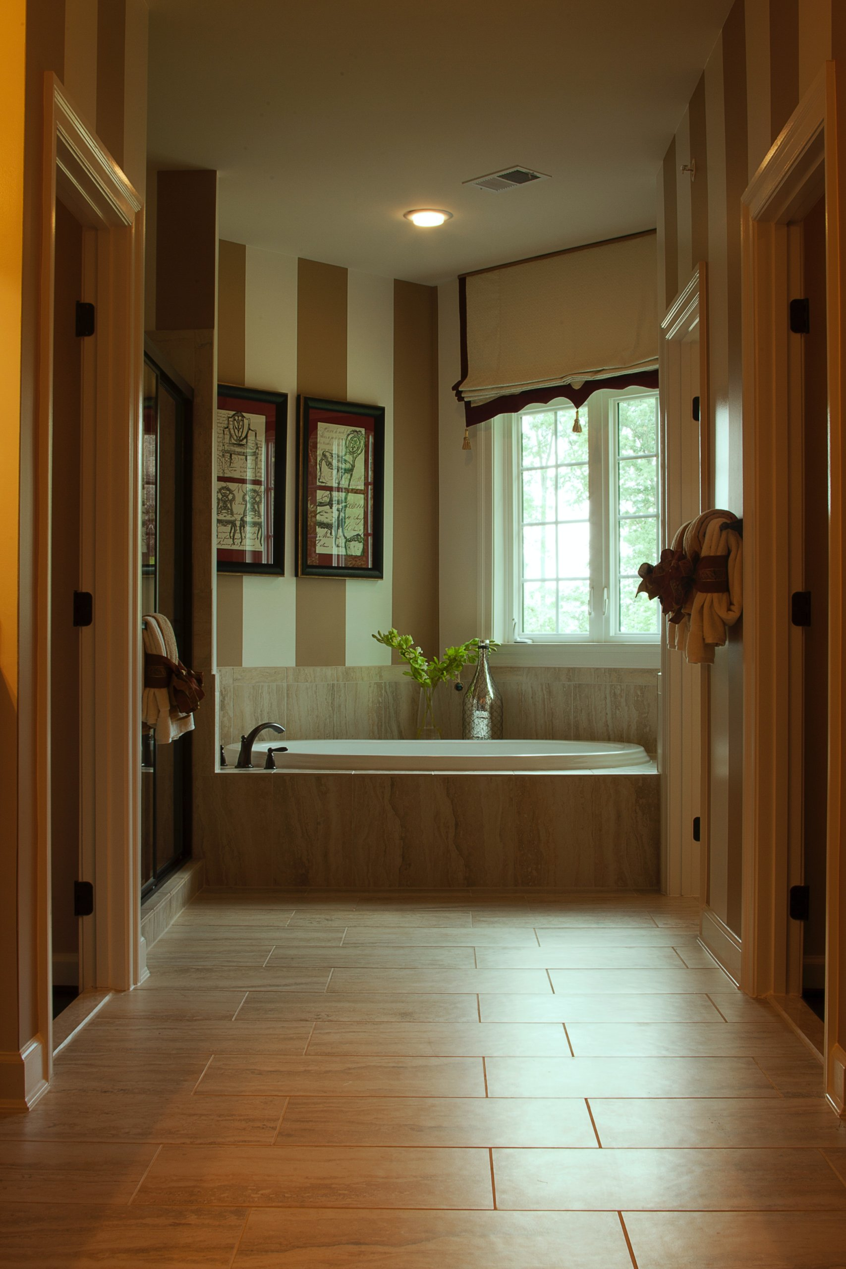 Neutral colored bathroom with frames and striped wall