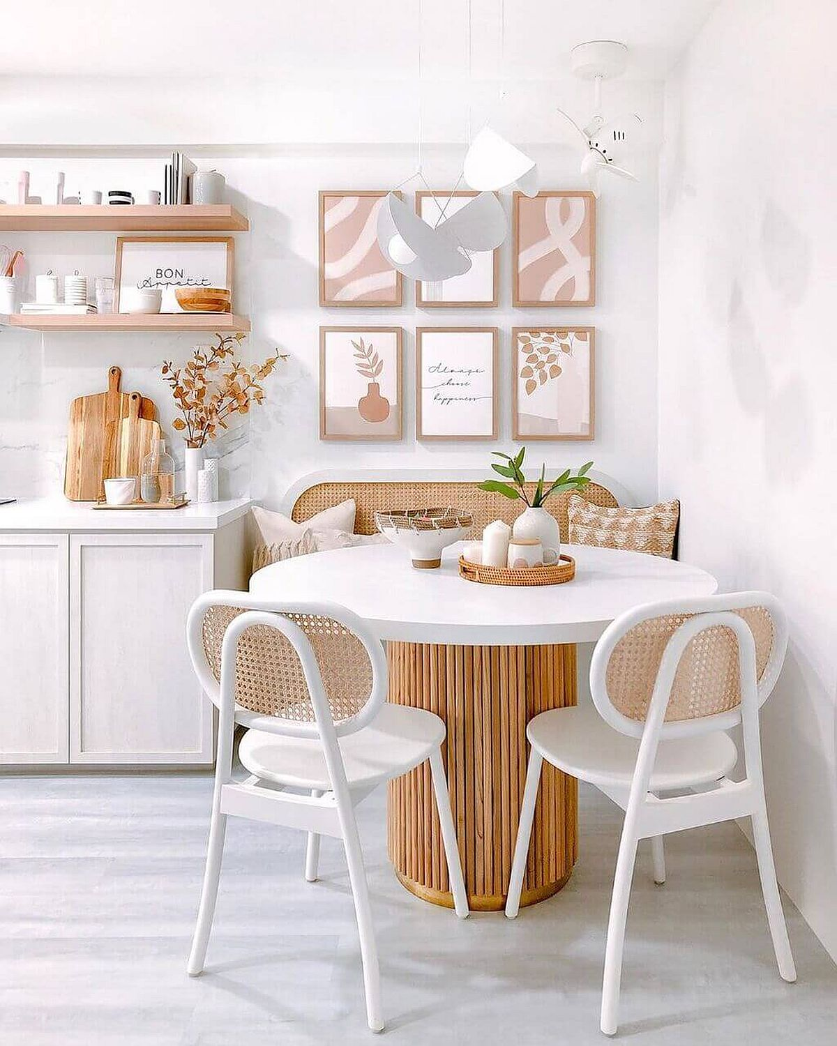 Picture-perfect white and wood dining room with a round dining table and pastel accents