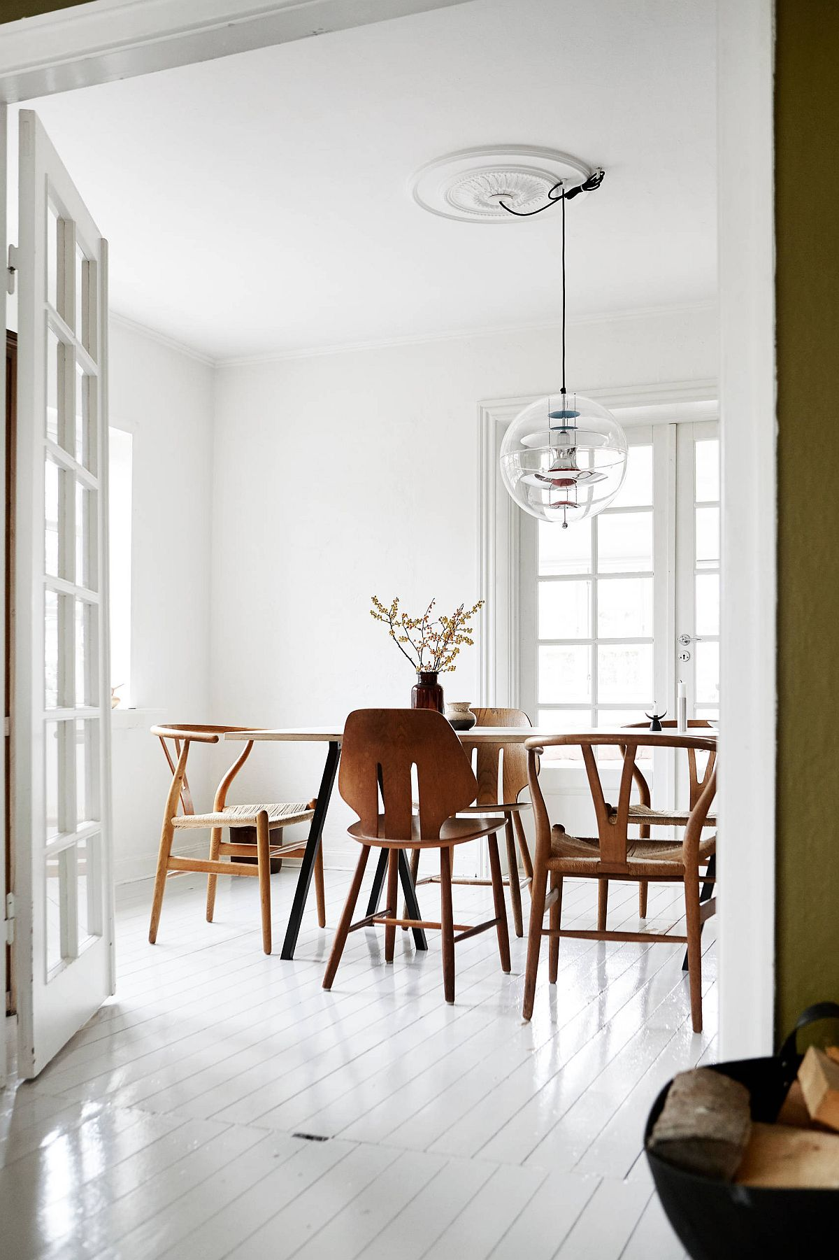 Polished and light-filled Scandinavian style dining room in white and wood