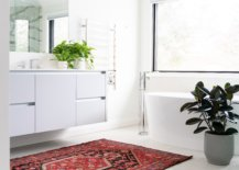 Red patterned rug in an all white bathroom with potted plants
