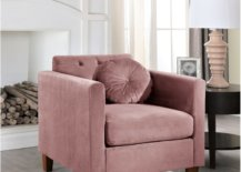 Rose color armchair with round cushion beside a table and a lamp