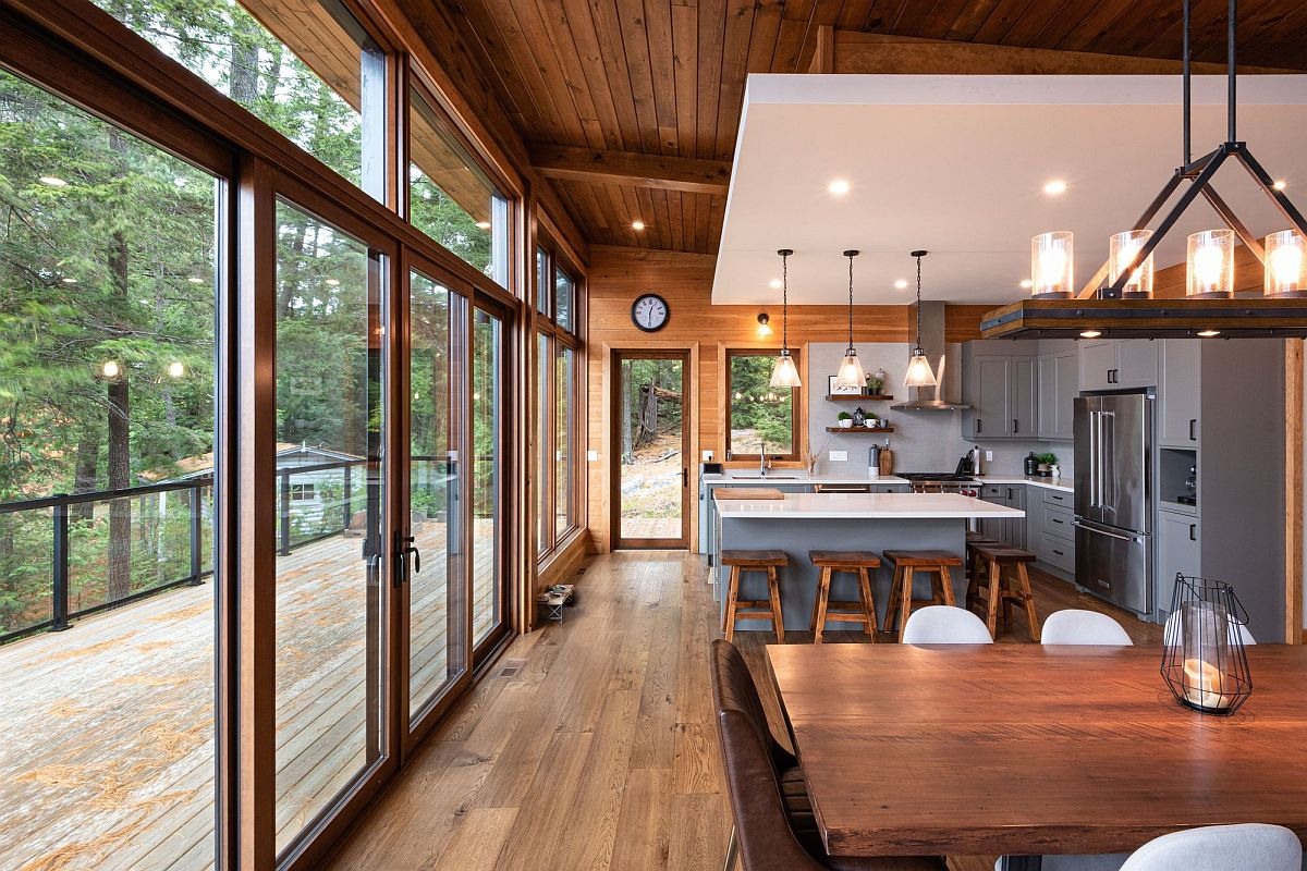 Series of sliding glass doors with wooden frames connect the new dining area and kitchen with the outdoors