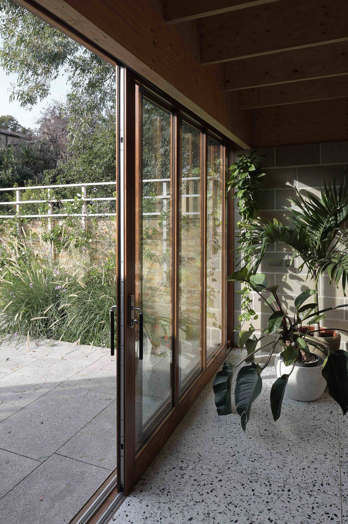 Sliding glass doors connect the interior with the garden outside