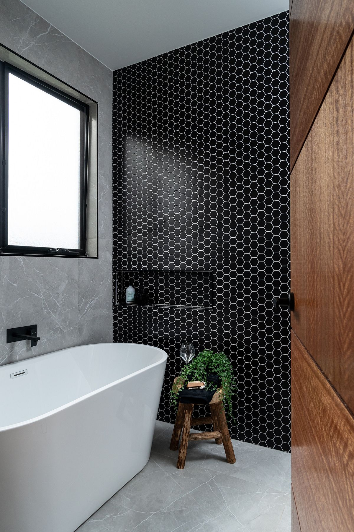 Small-hexagonal-tiles-in-black-steal-the-show-in-this-modern-bathroom-in-neutral-hues-90408