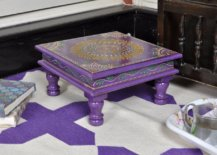 Small purple table with a purple and white carpet underneath