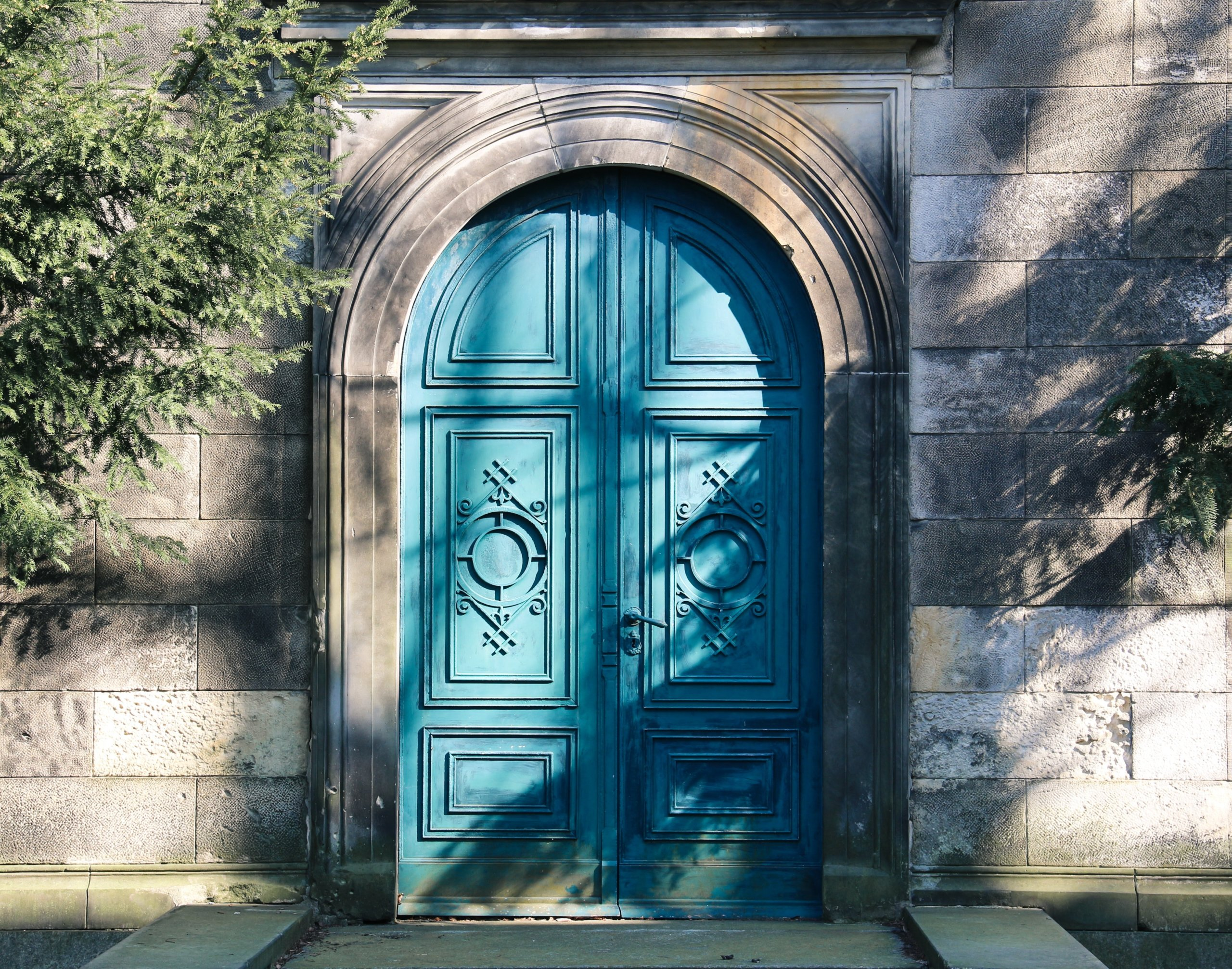 Turquoise arched door in gray wall