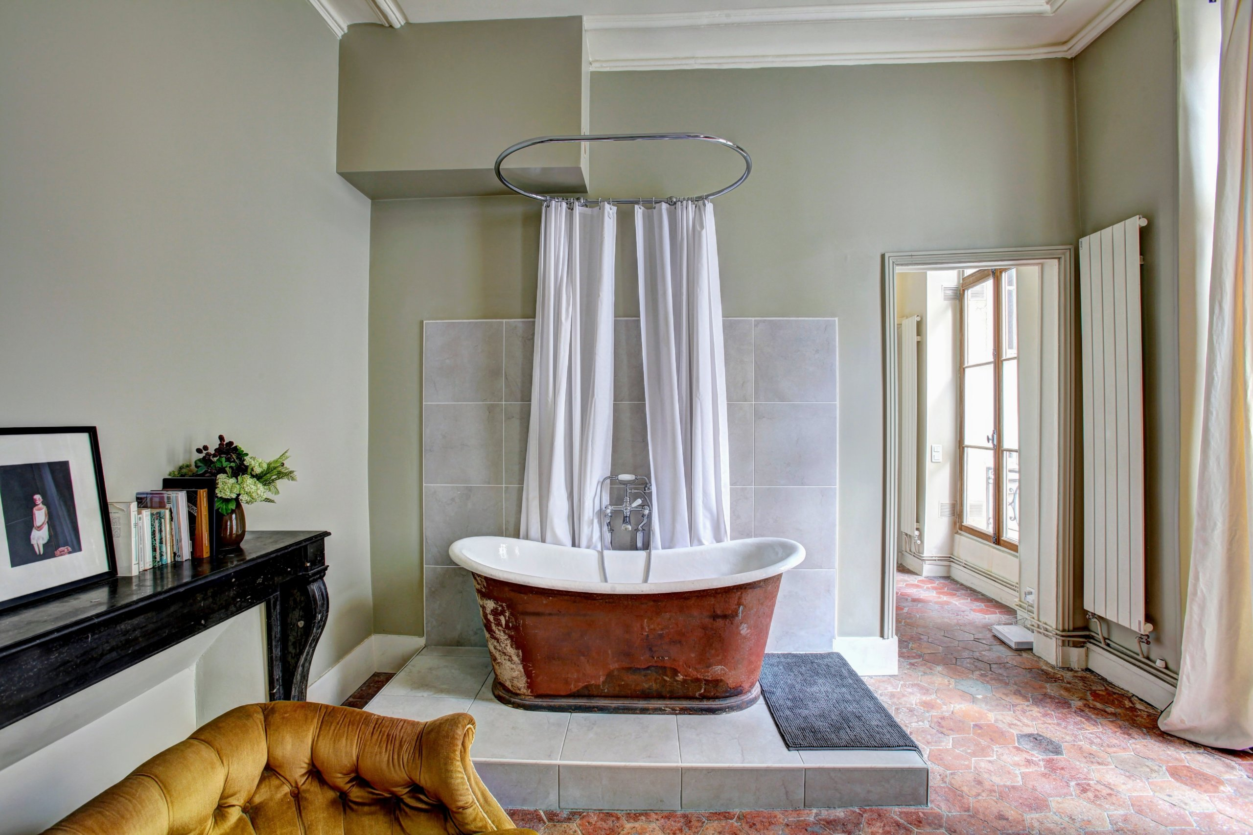 White and brown bath tub on top of elevated tile floor