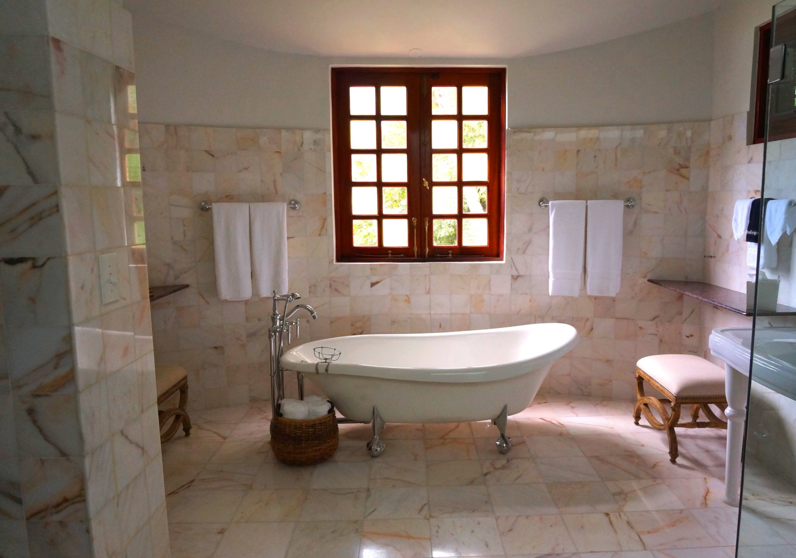 White bathtub in front of closed window