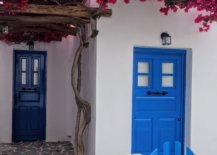 White exterior with blue door and pink flowers on top