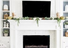 White fireplace with green and white decorations on the mantel