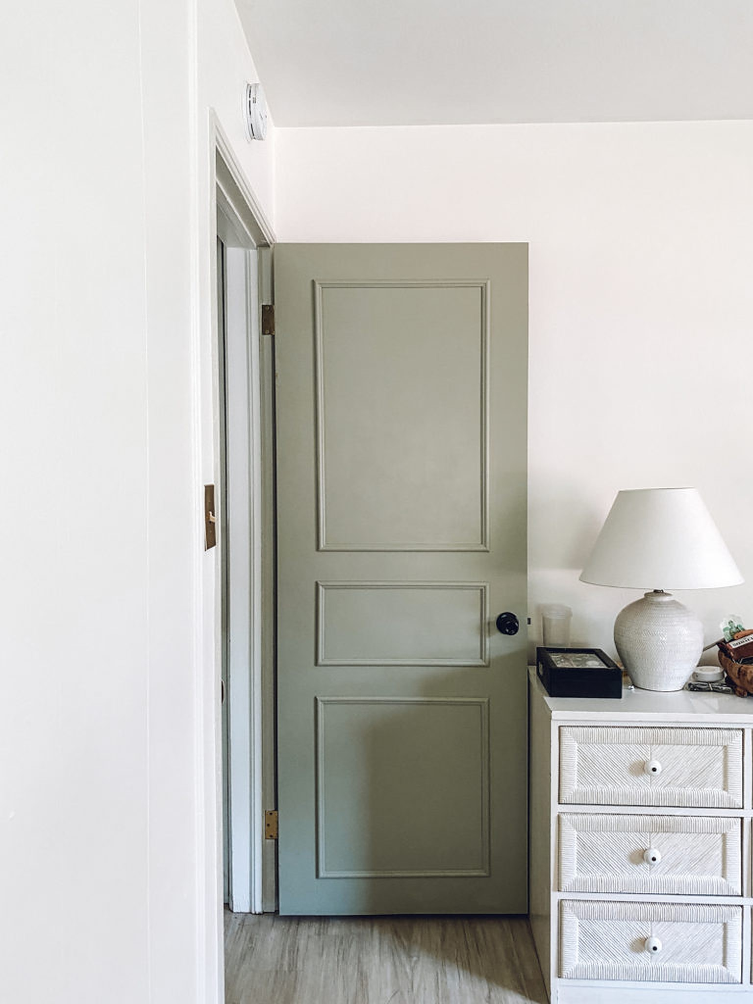 White lamp on white cabinet and an open door