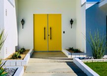 White wall with yellow door and black lamps
