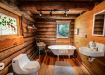 Wood bathroom walls and floor with white tub, white sink and white toilet