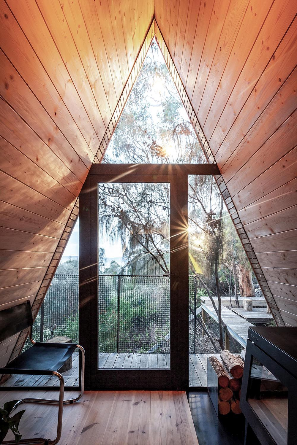 A-frame treehouse with glass walls and windows that bring the outdoor inside