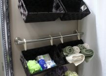 Baskets hanging on towel bars above toilet