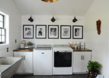 Black and white photos hanging on the wall in the laundry room
