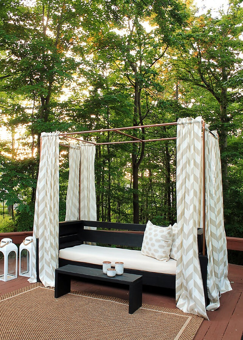 outdoor sofa with curtains hanging from copper pipes