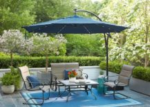 Blue cantiveler umbrella over metal chairs and tables