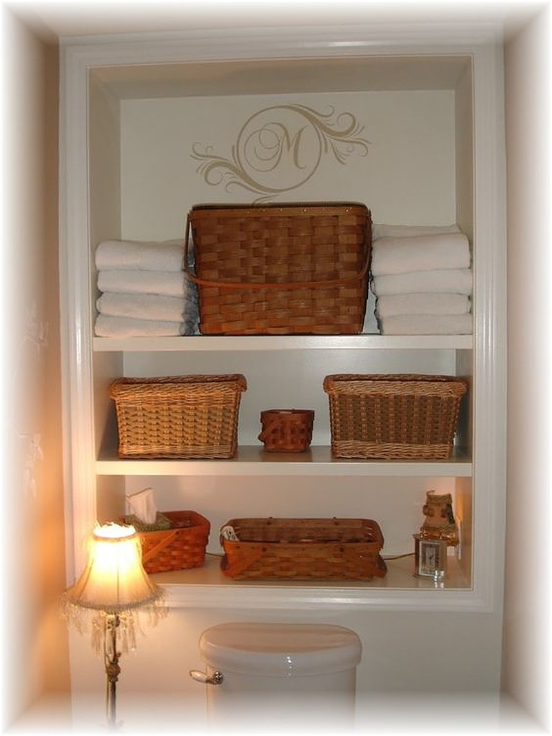 Brown baskets on white shelf above toilet