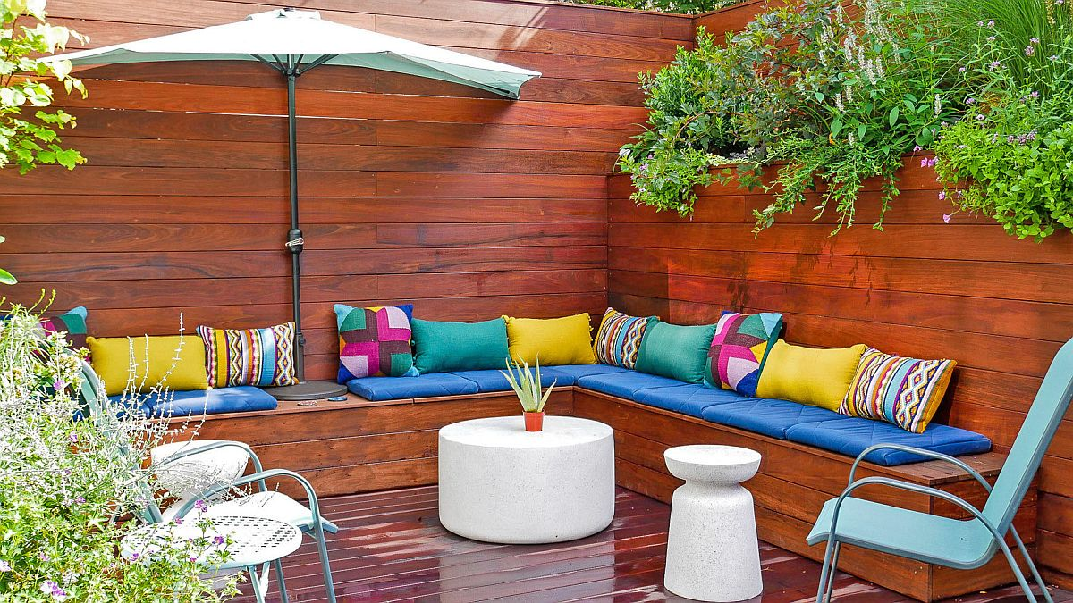 Colorful cushion and multi-colored pillows enliven this small contemporary deck with built-in seat