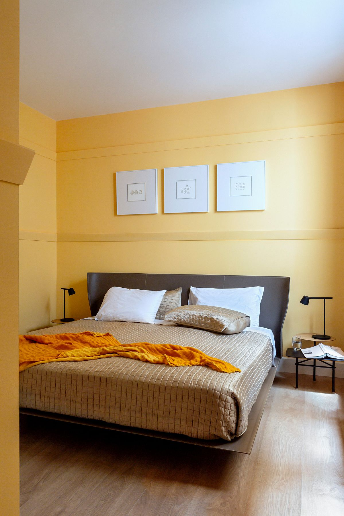 Contemporary bedroom in white and yellow with wooden floor