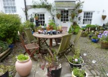 Cottage with table and chairs surrounded by potted plants