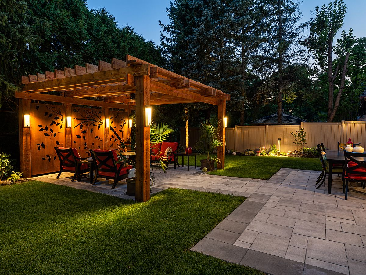 Custom wooden panels with apttern and warm lighting shape this tropical style pergola