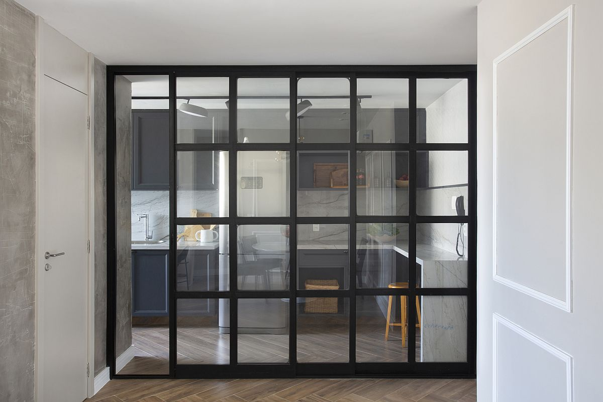 Dark-framed sliding glass doors separate the living area from the kitchen