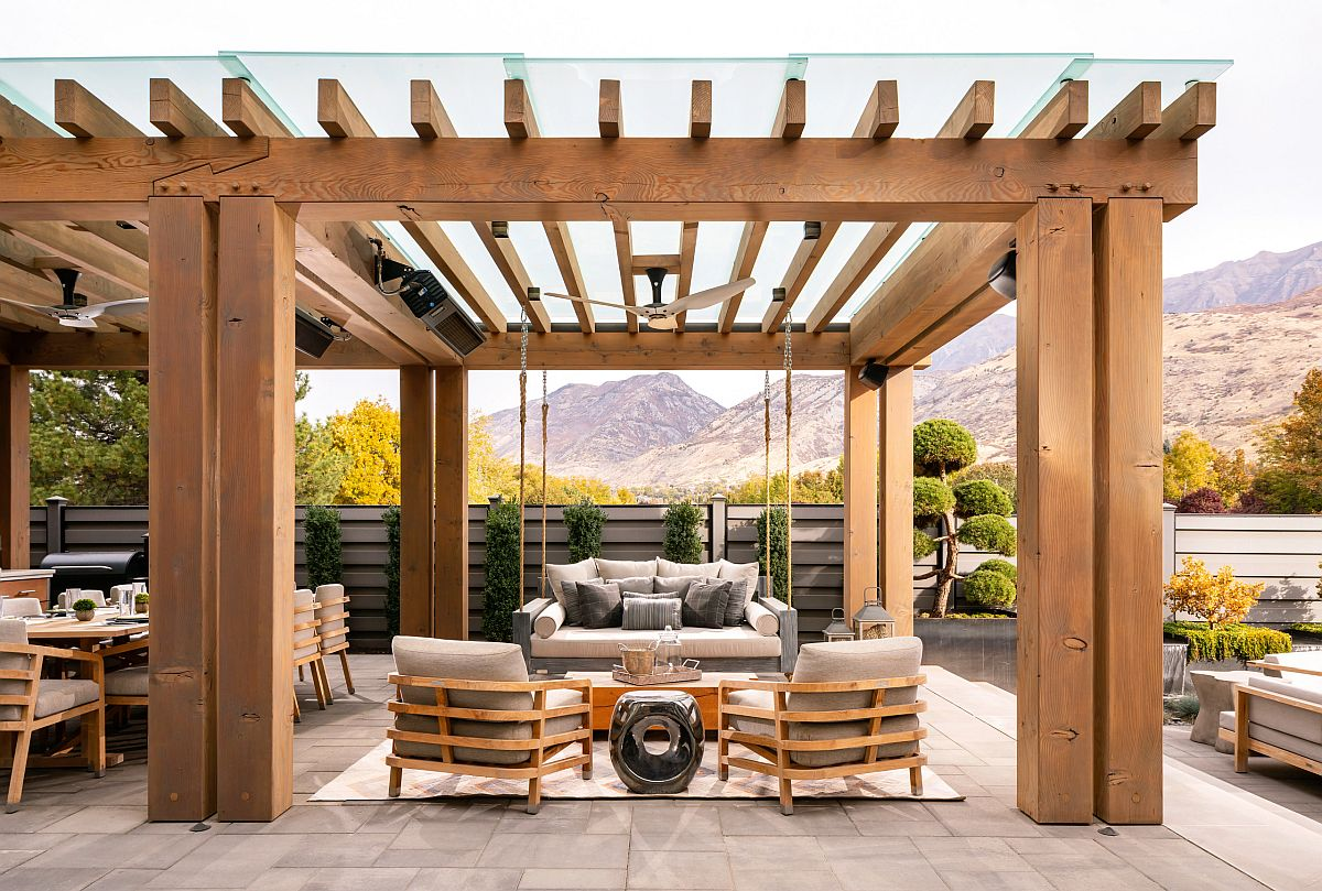 Exquisite wooden pergola structure with ceiling fan and comfy outdoor decor