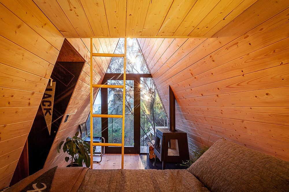 Fireplace coupled with bunk beds and cozy nooks inside the modern treehouse