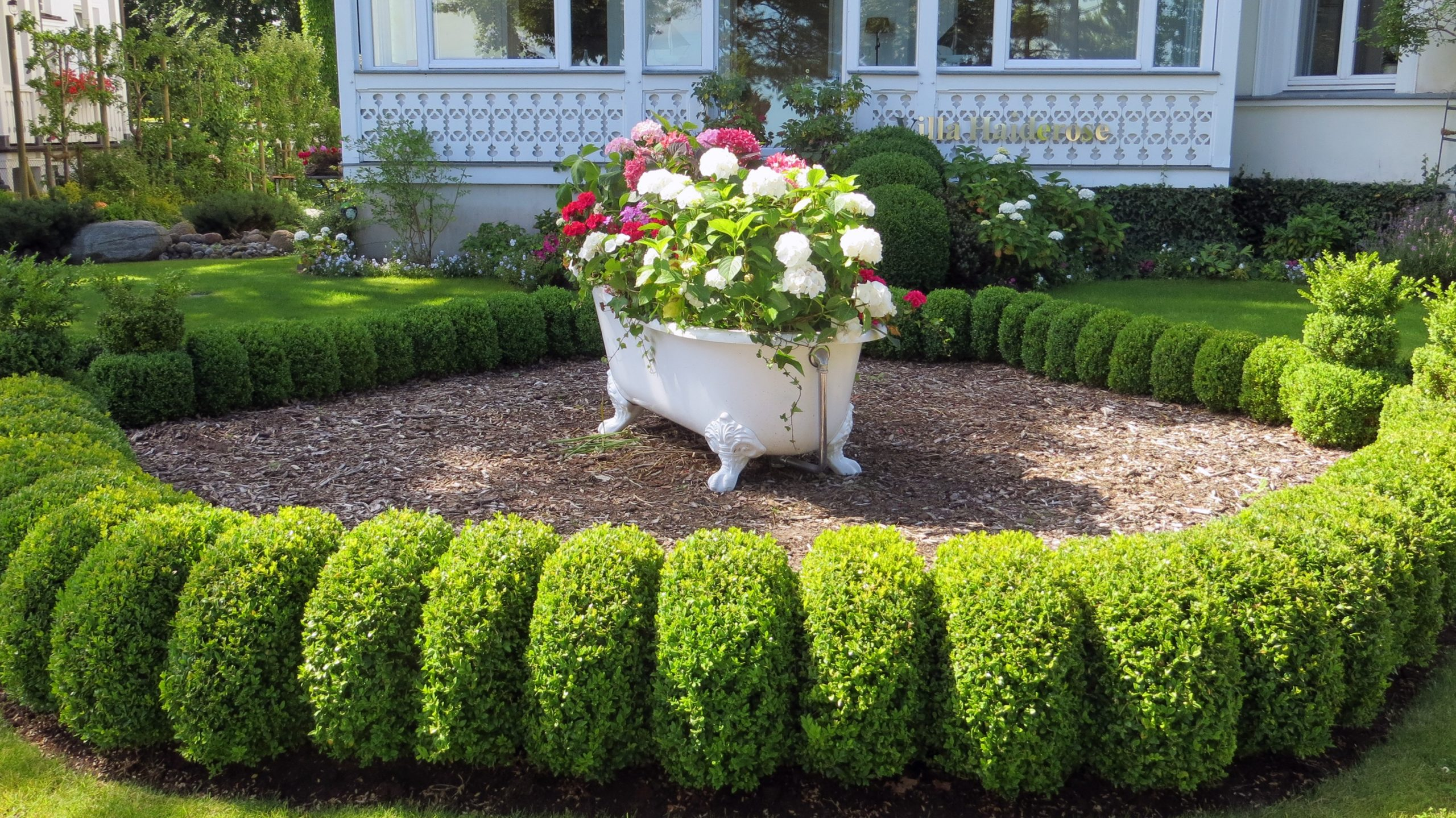 Flowers on a tub surrounded by well-maintened hedges