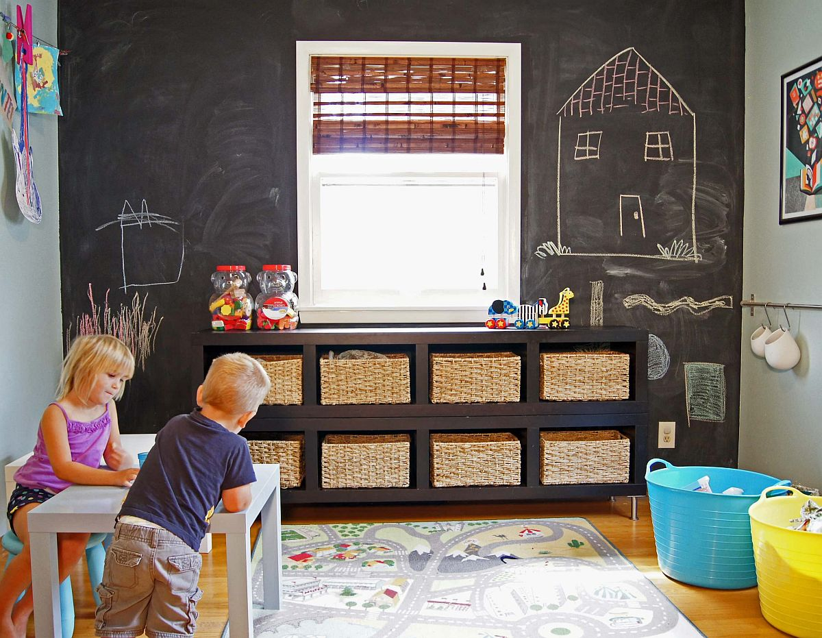Fun playroom with small storage baskets for toys and a chalkboard wall in the backdrop