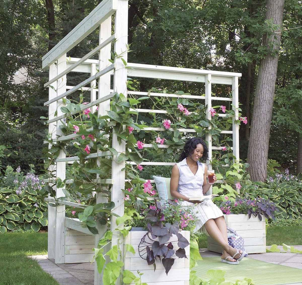 woman sitting on bench with hanging flowers