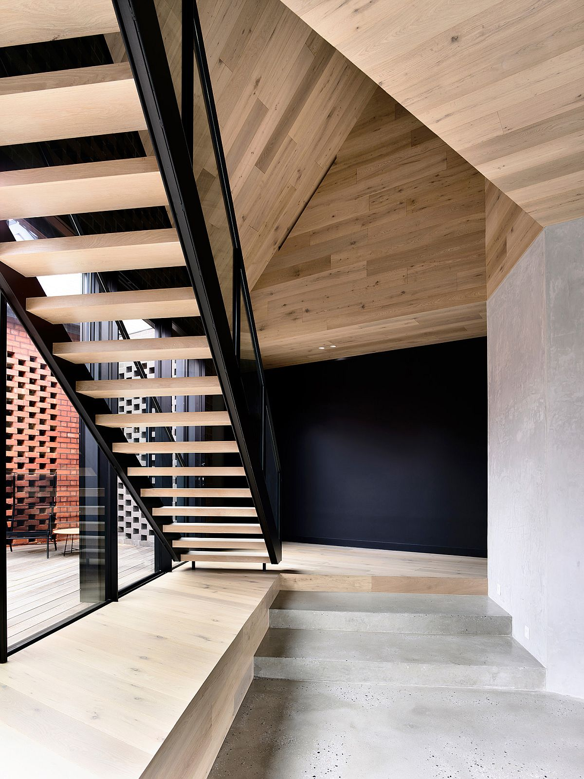 Glass walls bring natural light into the home with a new, sculptural staircase