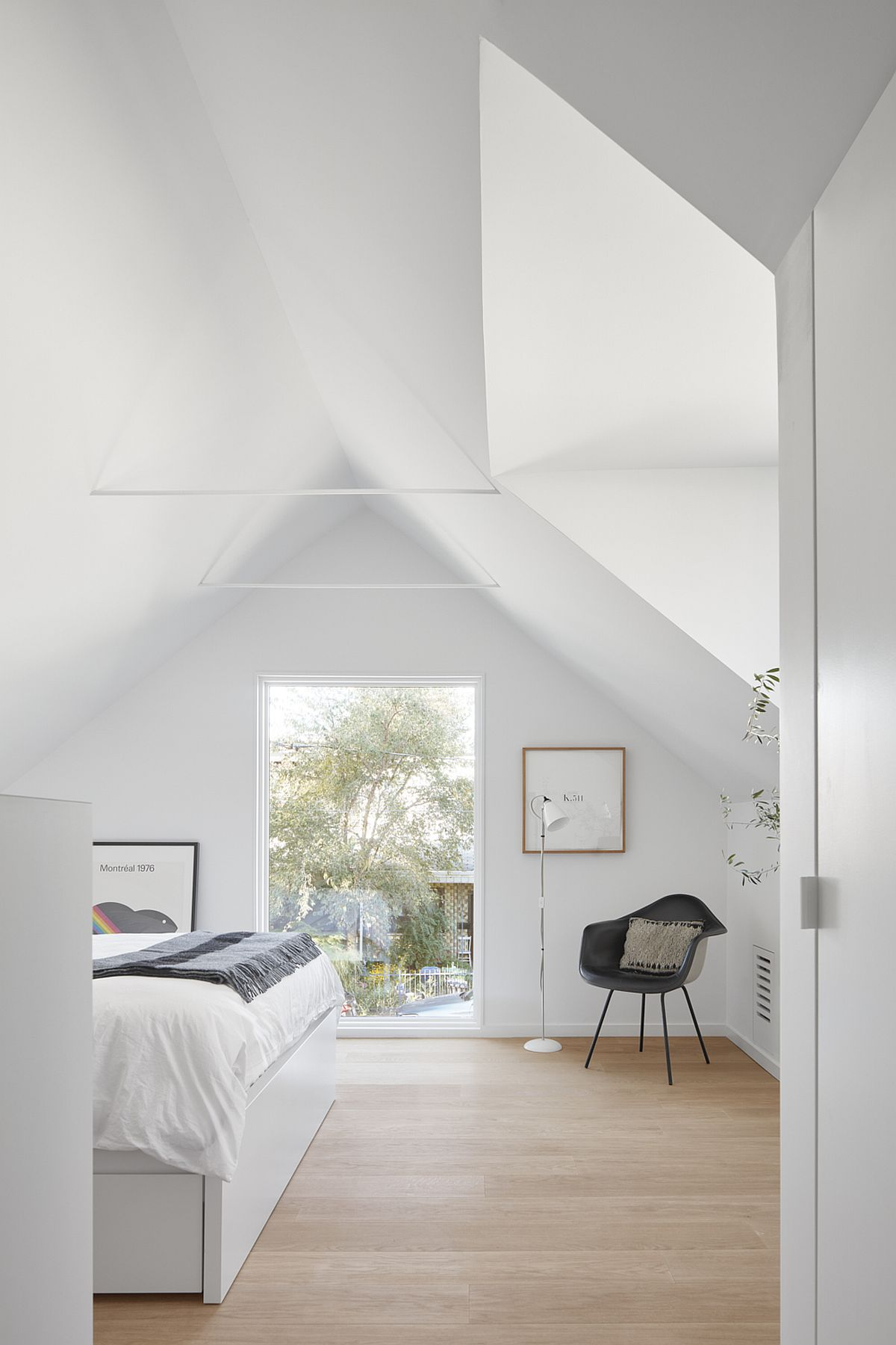 Glass window and skylight bring ample natural light into the bedroom on the upper level