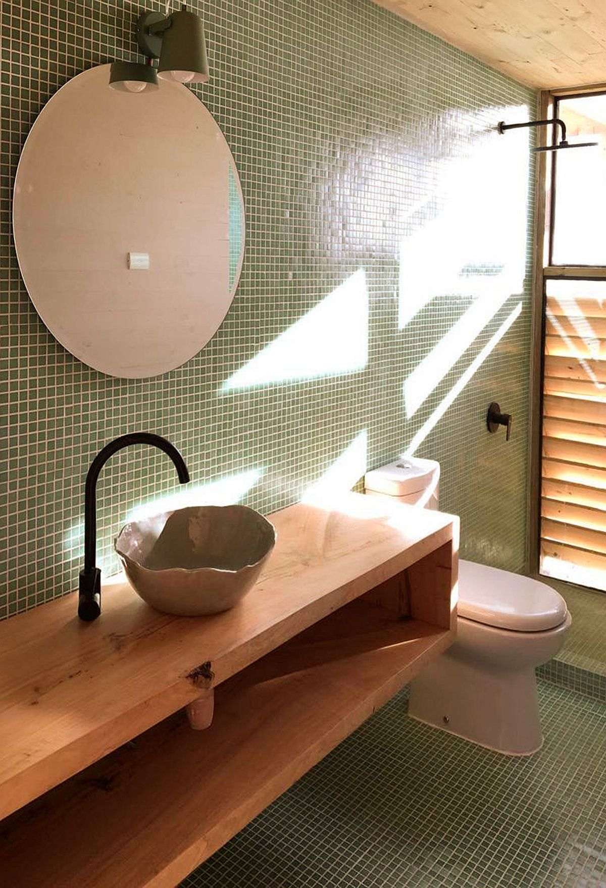 Green tiles in the bathroom add color to the modern space