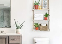Hanging shelf with plants and towels above the toilet