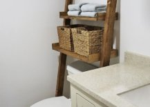 Ladder storage shelf leaning on the wall with wicker baskets and towels