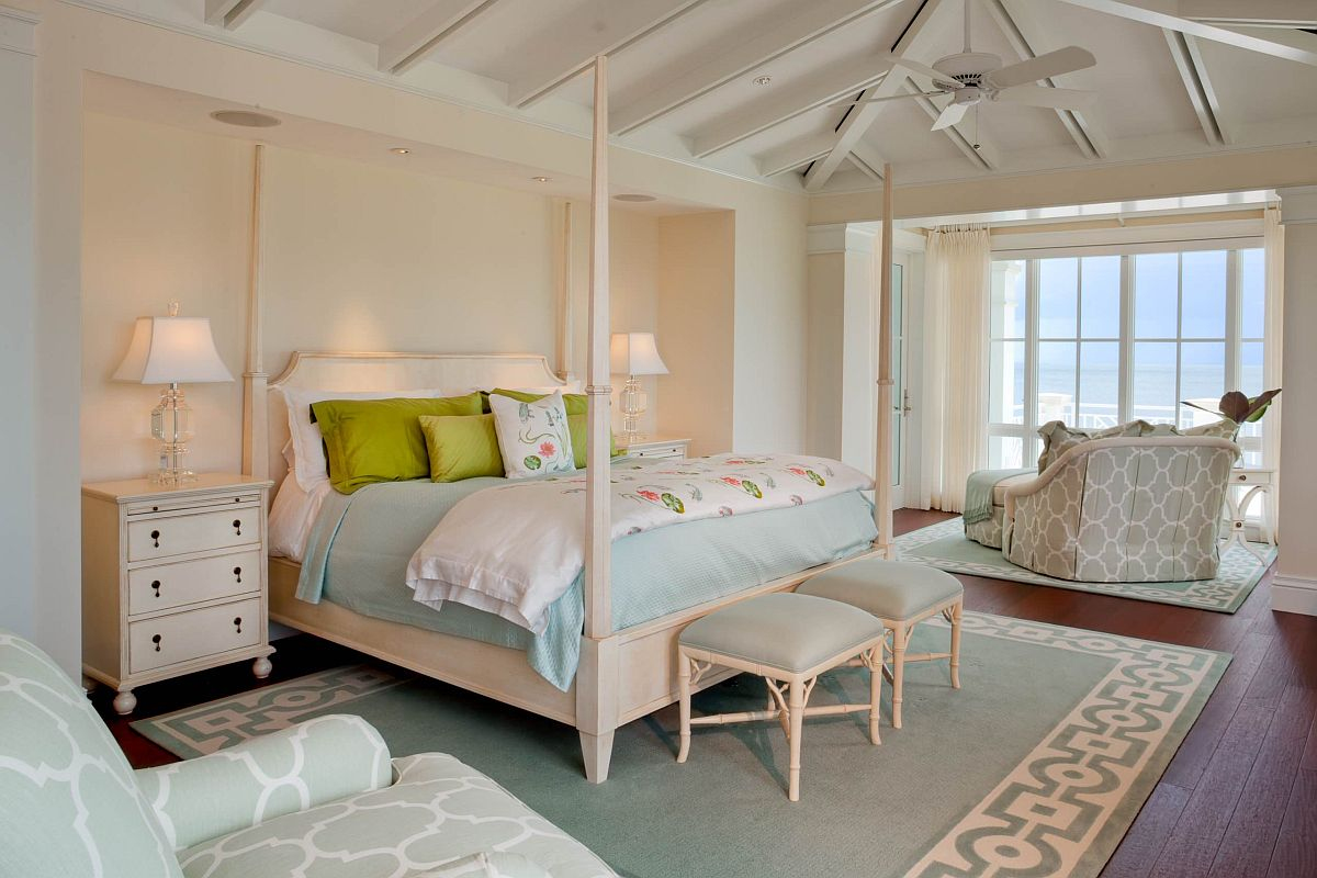 Large and lavish tropical style bedroom with an accent pastel pink wall