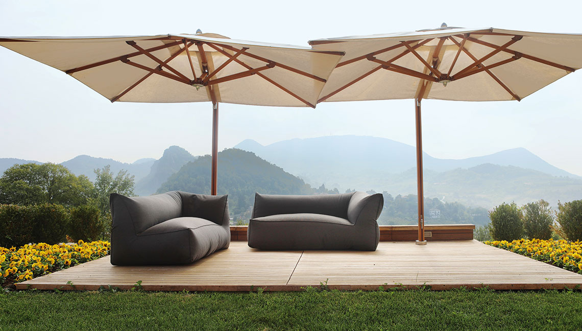 Large umbrellas shading two sofas on deck