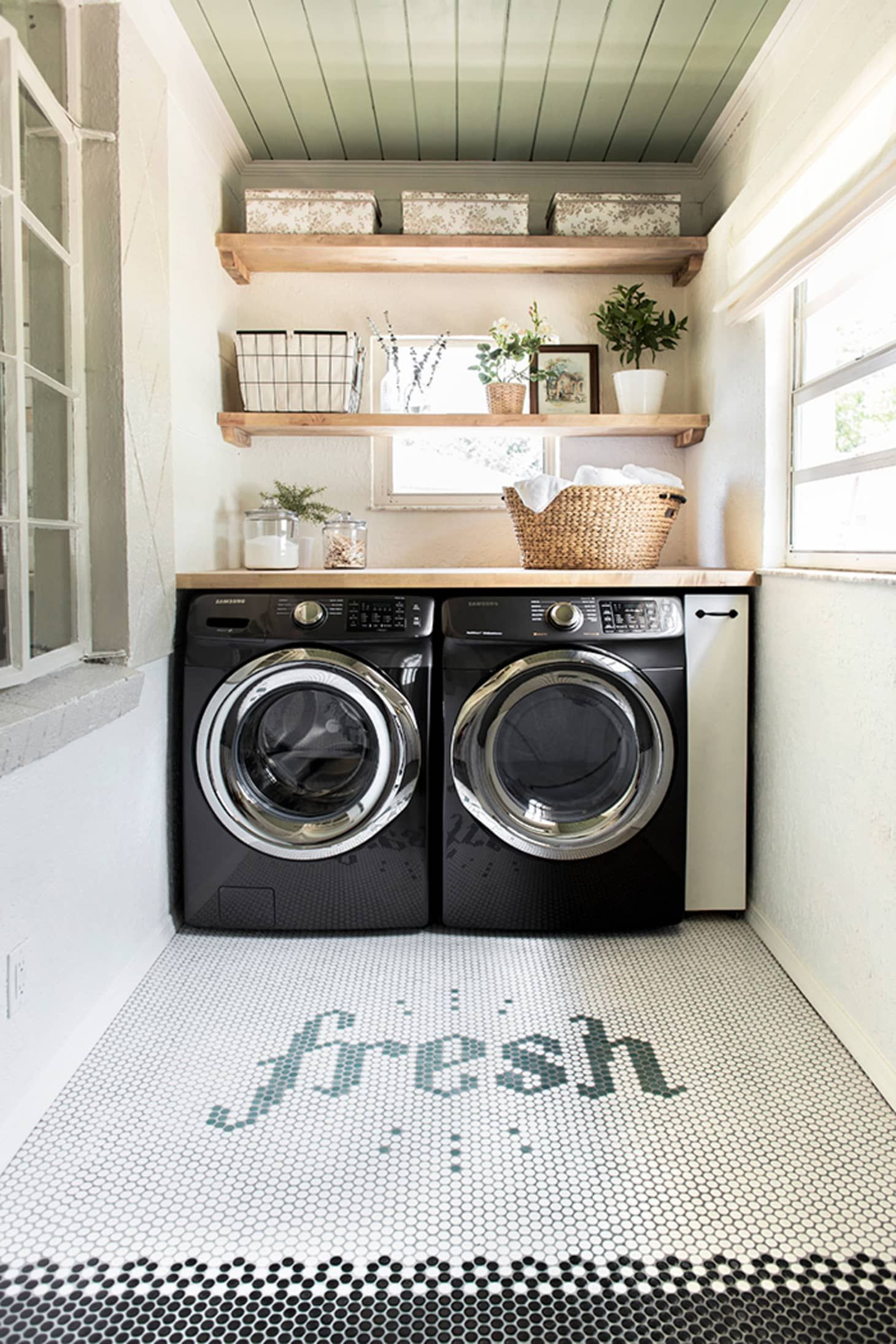 Laundry room with black washer and dryer and penny tile floor design